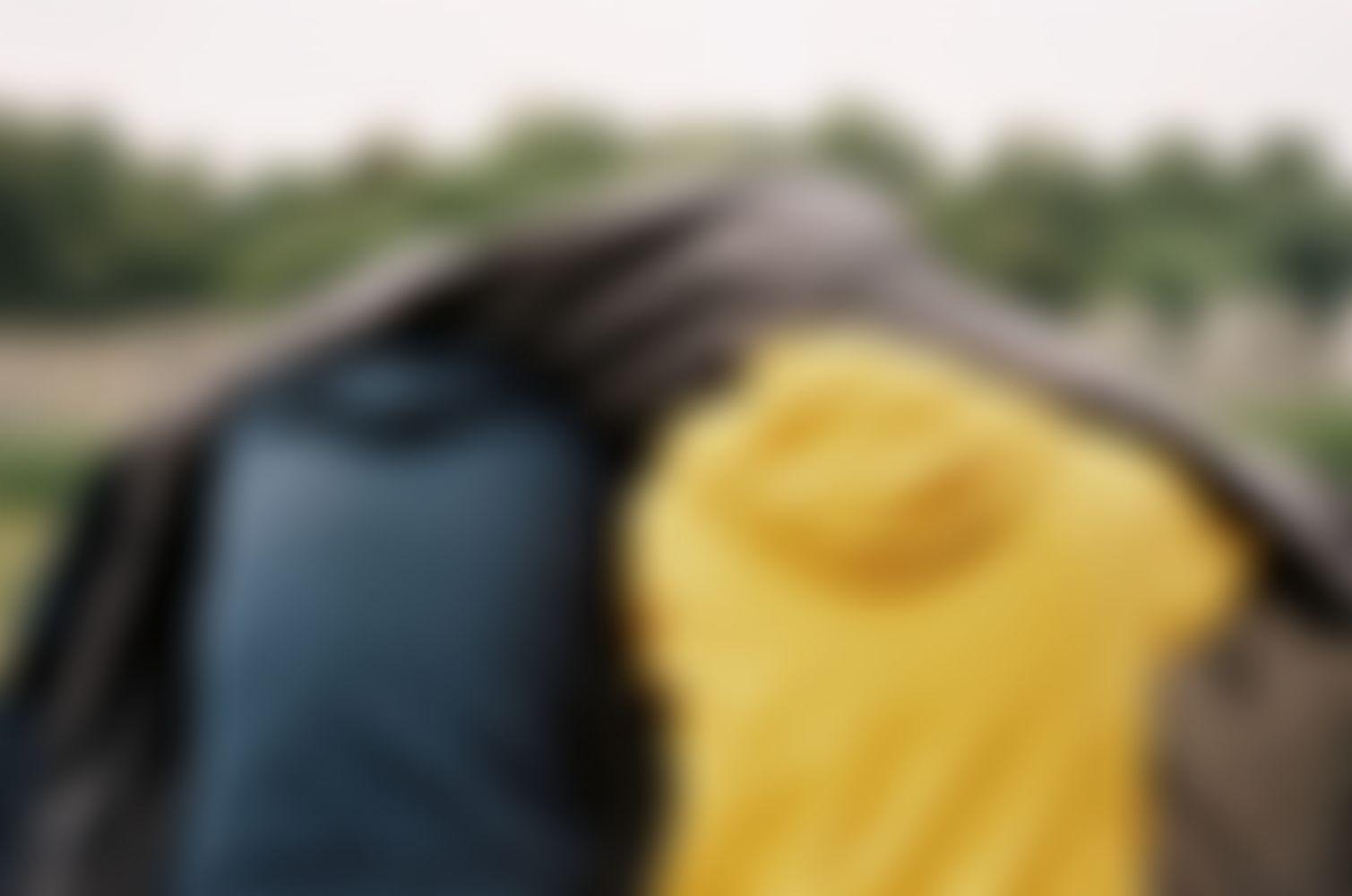 zwei aneinander lehnende Personen sind von hinten zu erkenne, sie schützen sich mit Jacken vor dem Regen