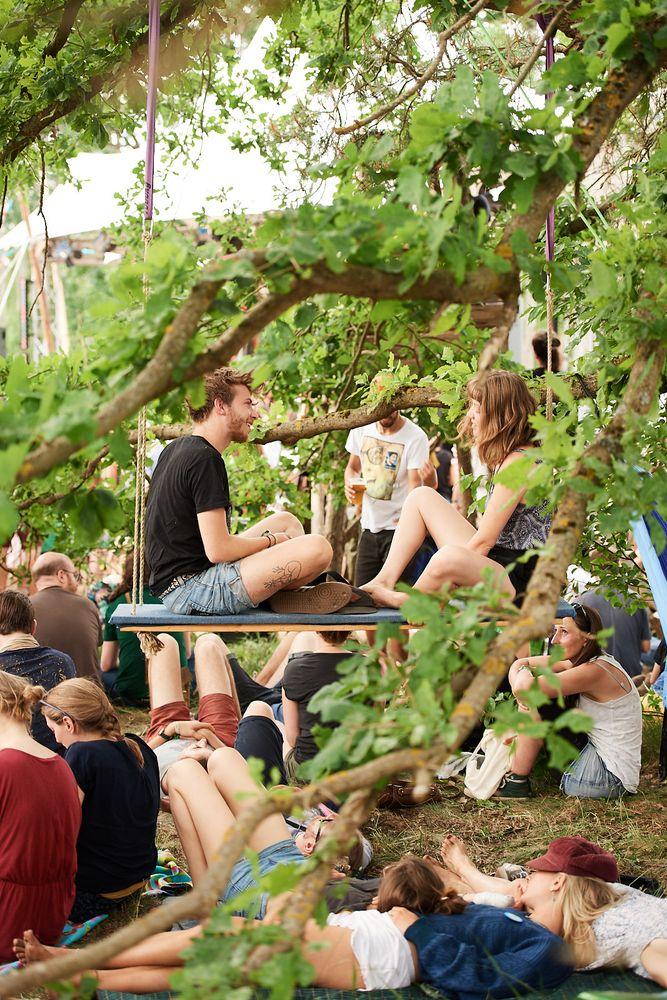 Menschen sitzen auf einer Schaukel im Baum, umgeben von Publikum