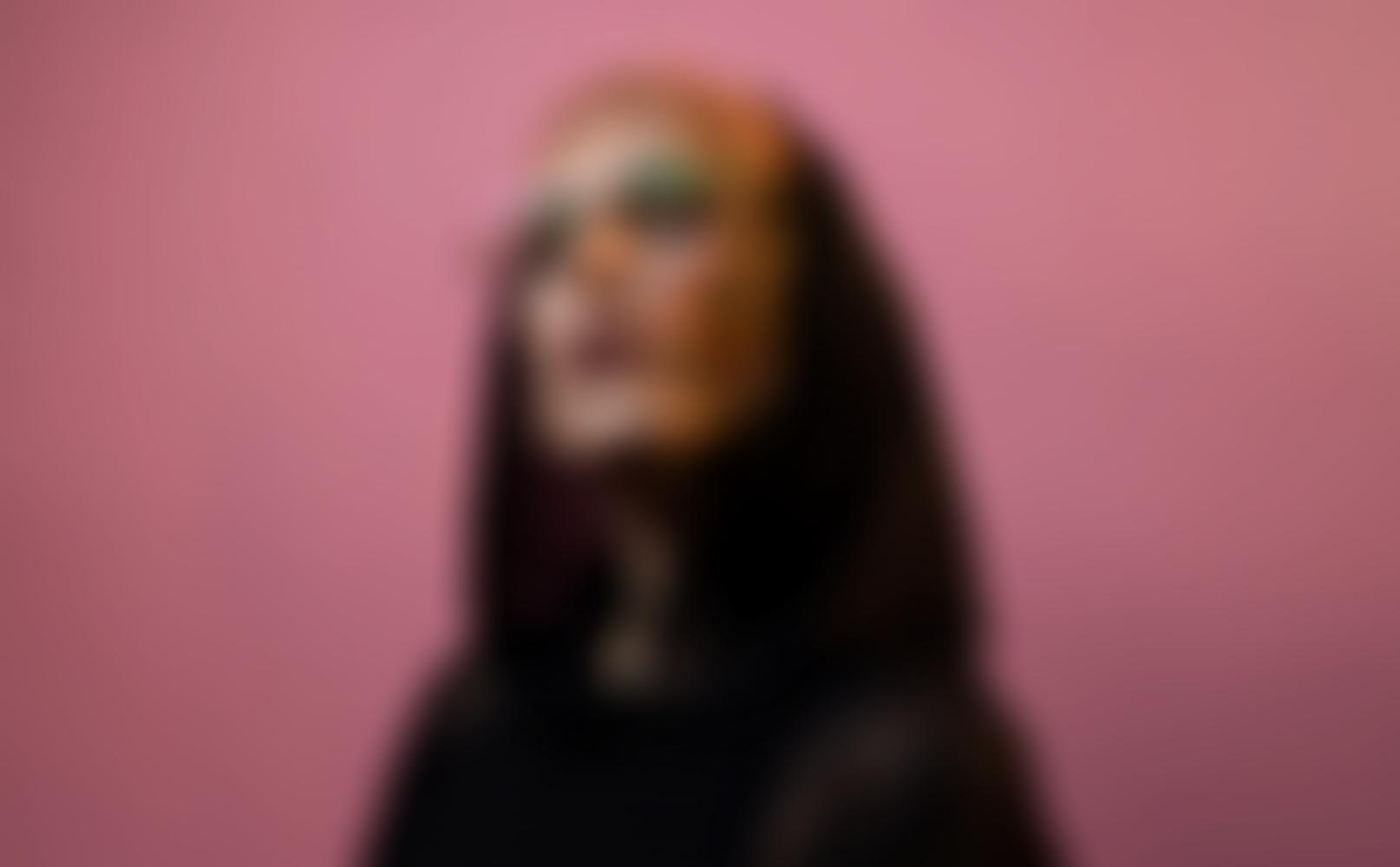 Portrait der Künstlerin Mine vor rosa farbiger Wand, sie trägt schwarzes Oberteil mit Kapuze und schaut Richtung Kamera