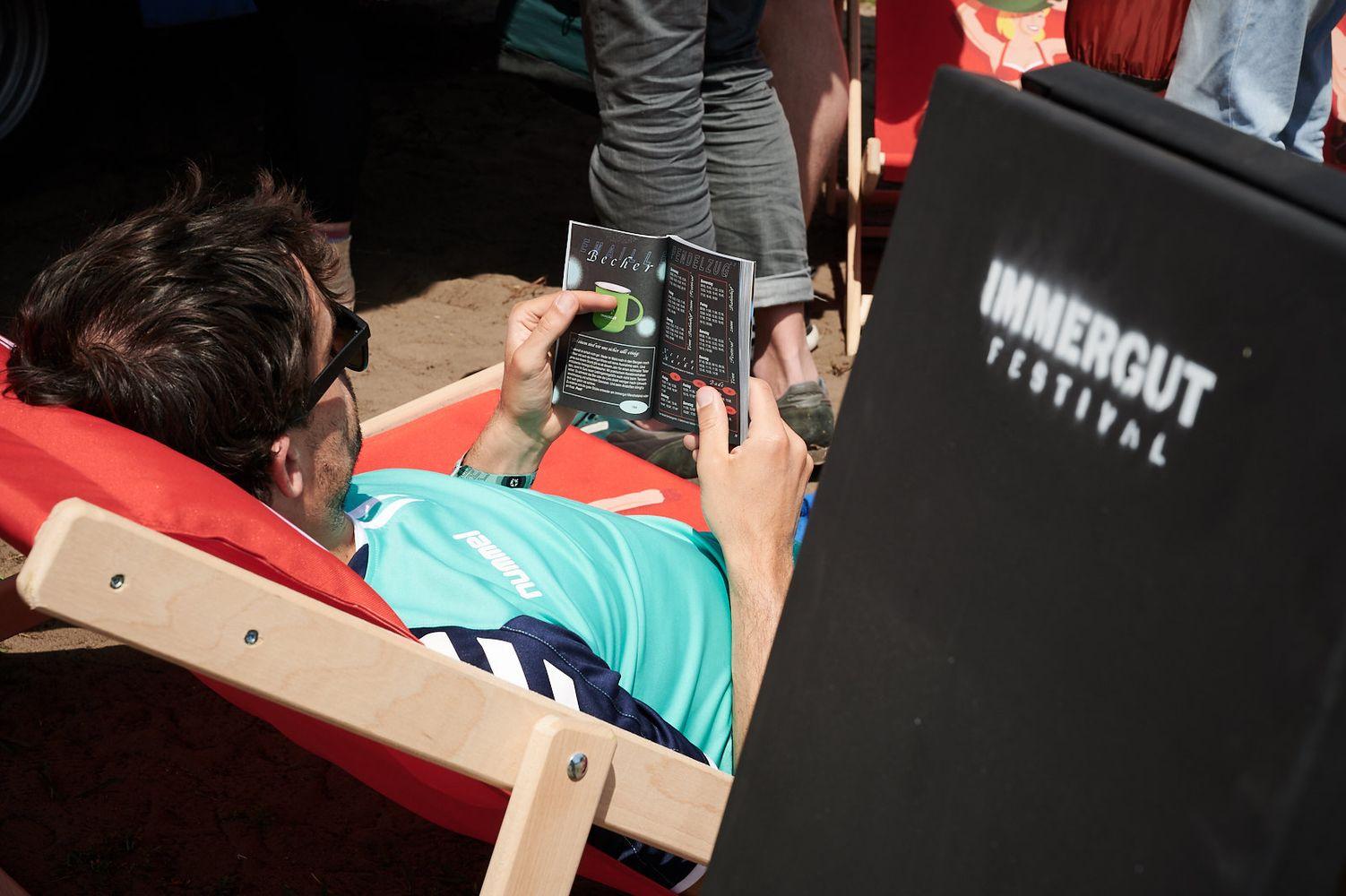 Mensch auf einem Liegestuhl liest das Begleitheit