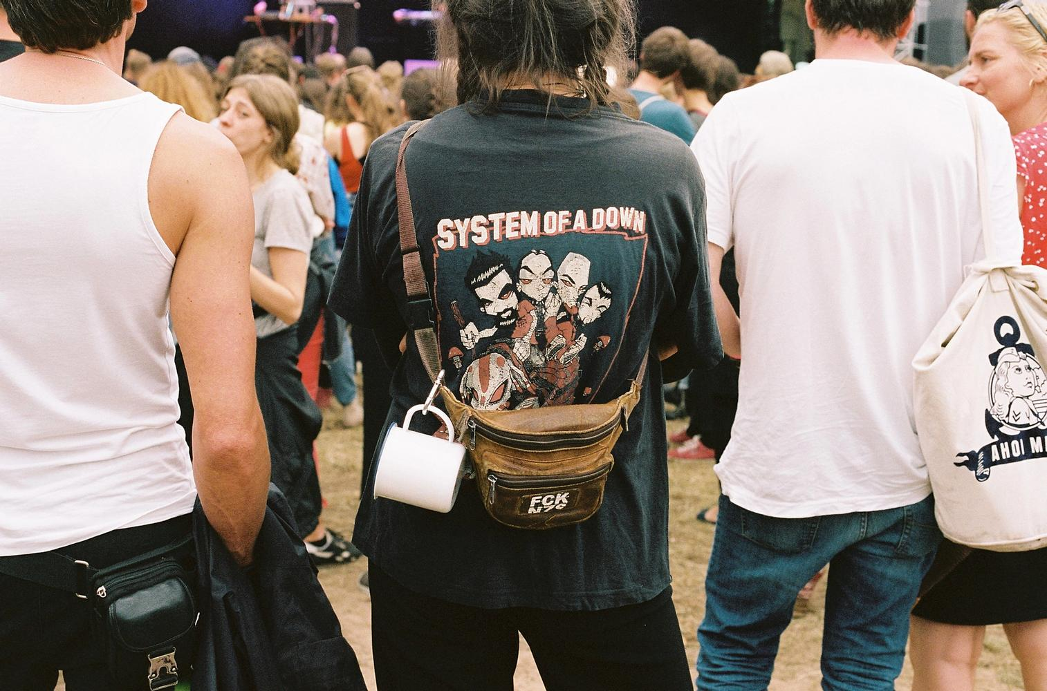 Person von hinten vor der Waldbühne stehend, Emailletasse hängt an Bauchtasche