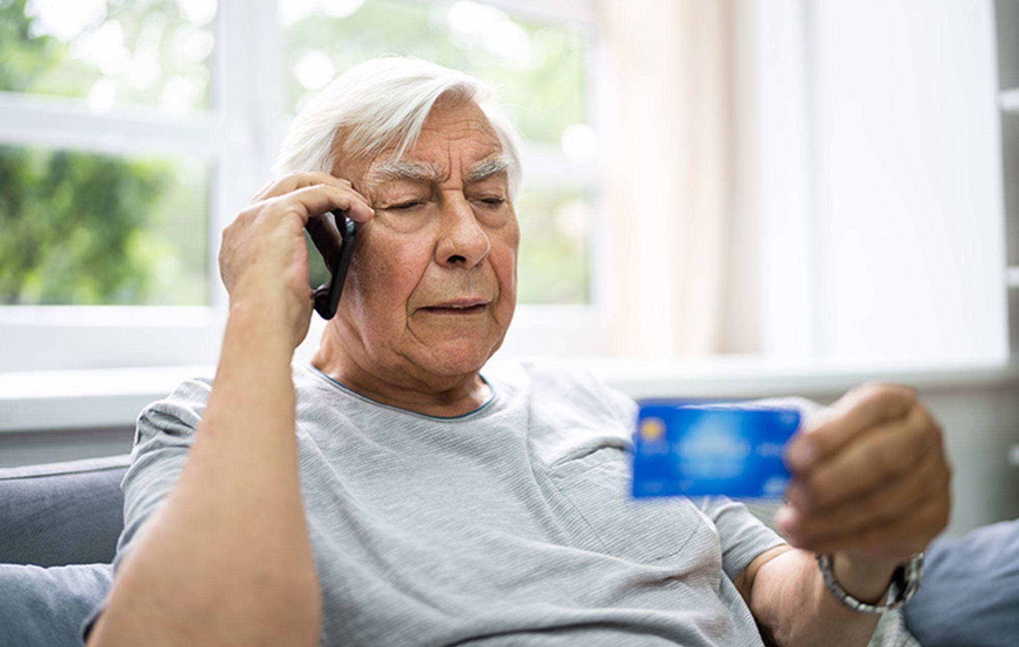 Äldre man pratar i mobiltelefon samtidigt som han tittar på ett betalkort
