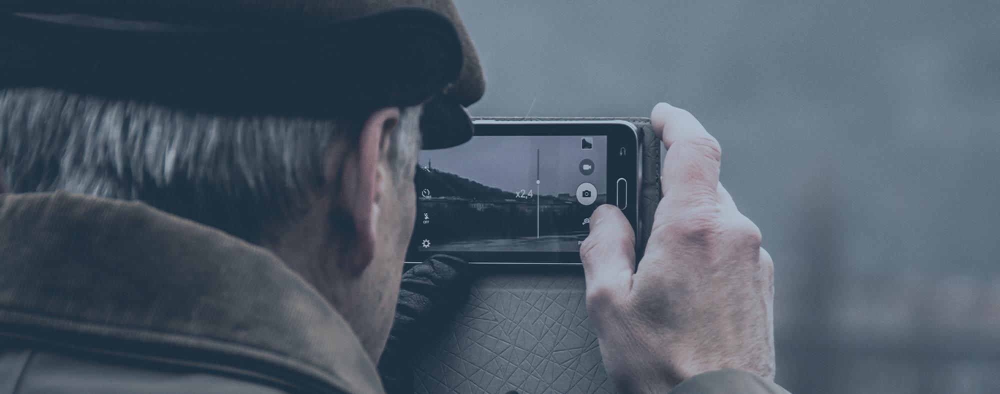 Äldre man med mobiltelefon tar en bild