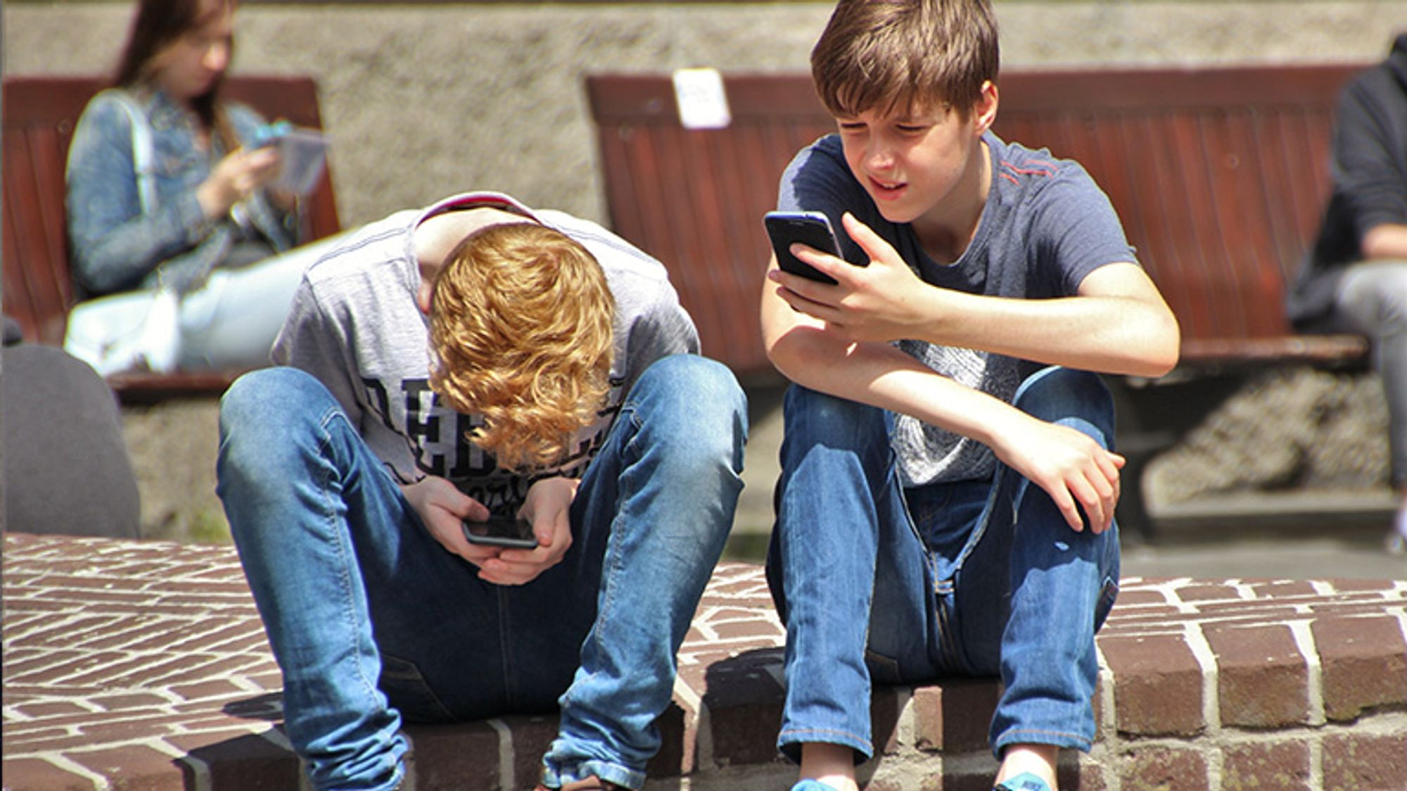 Två pojkar som sitter utomhus och tittar på sina mobiltelefoner