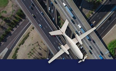 Jet plane flying above automotive highway traffic