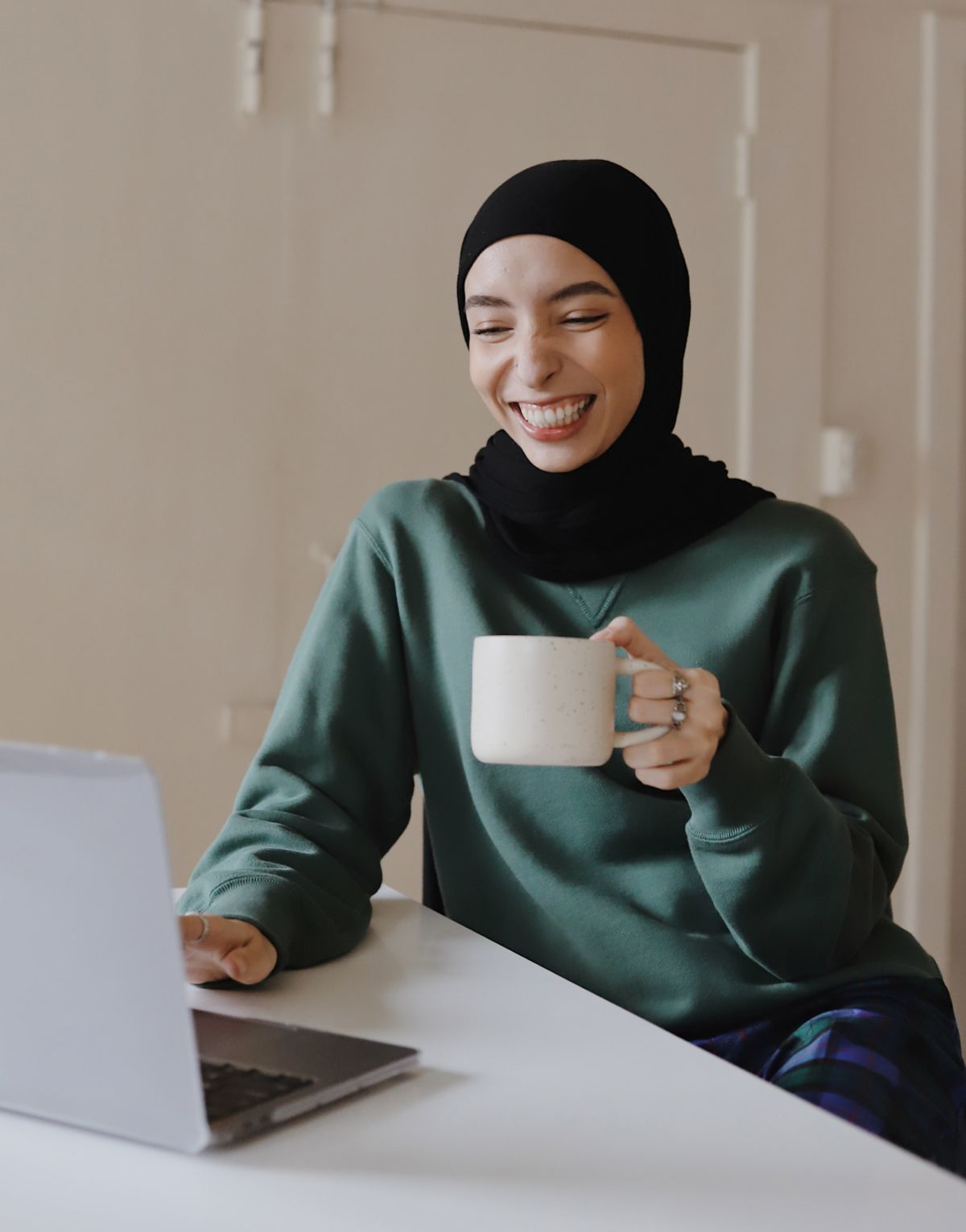 A laughing woman sits in front of her computer
