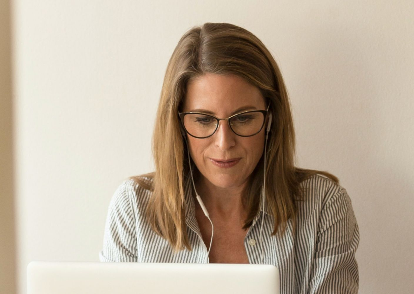 A woman with earphones works on her laptop computer