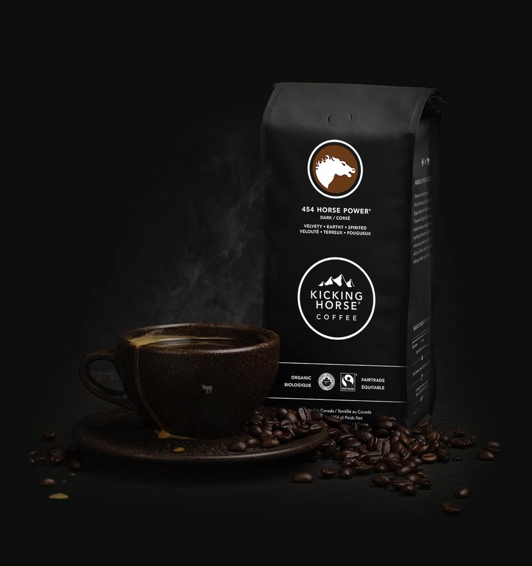 A cup of coffee, with a bag of coffee and some coffee beans