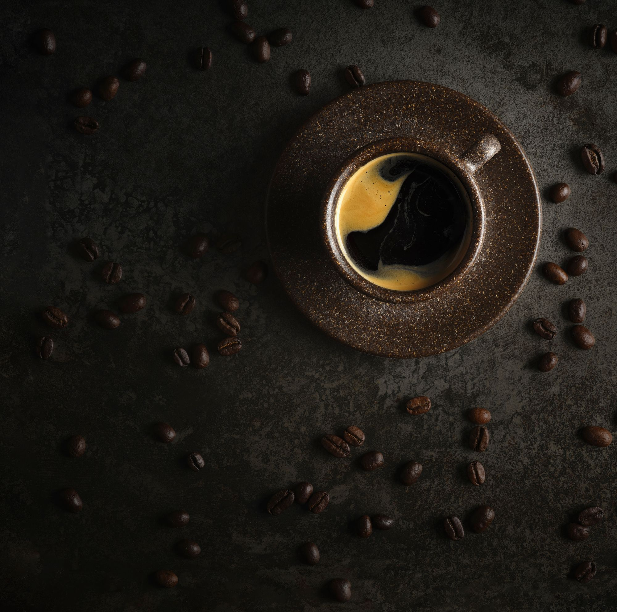 Overhead image of black coffee with whole beans in the background