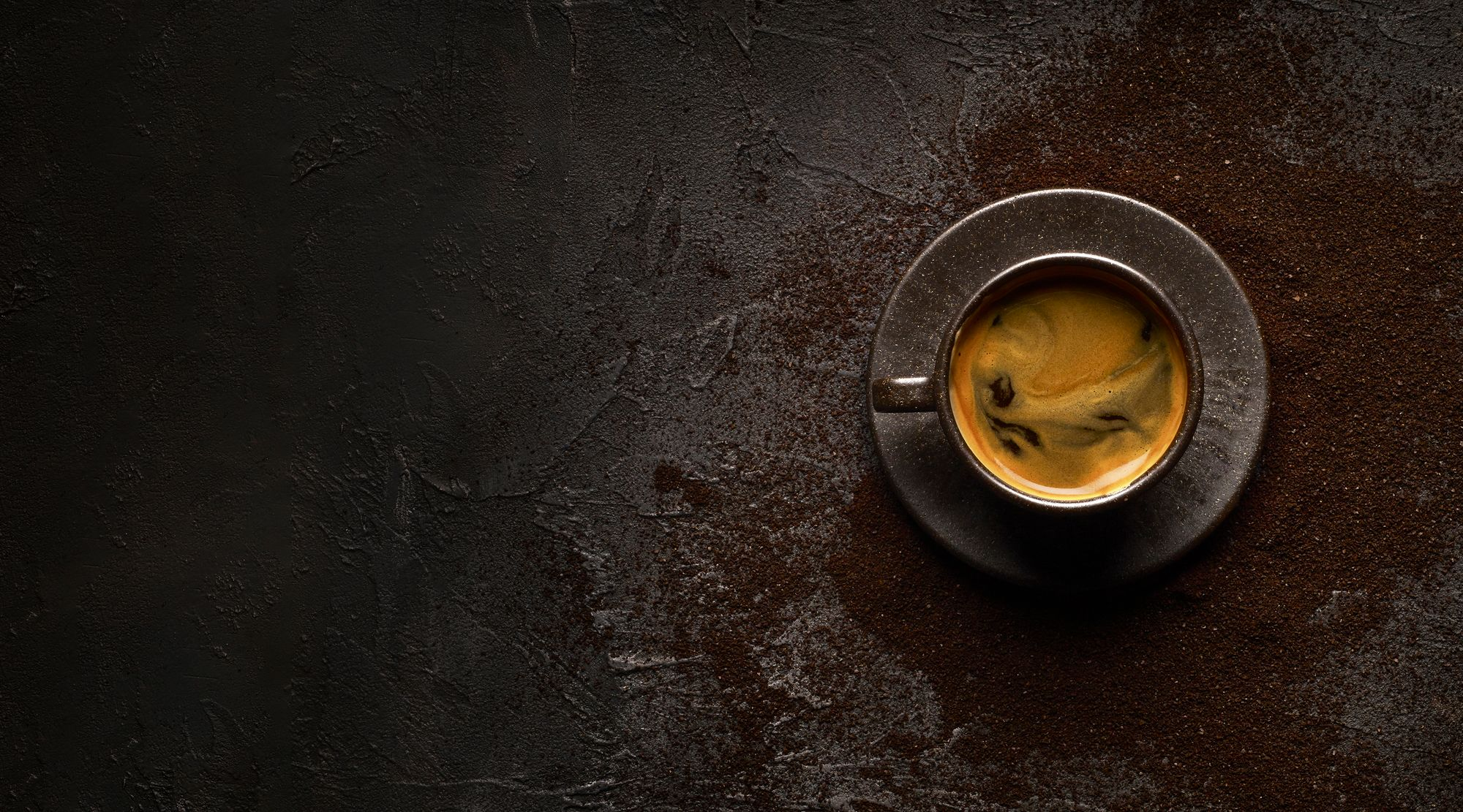 overhead shot of cup of coffee with crema and grounds in the background