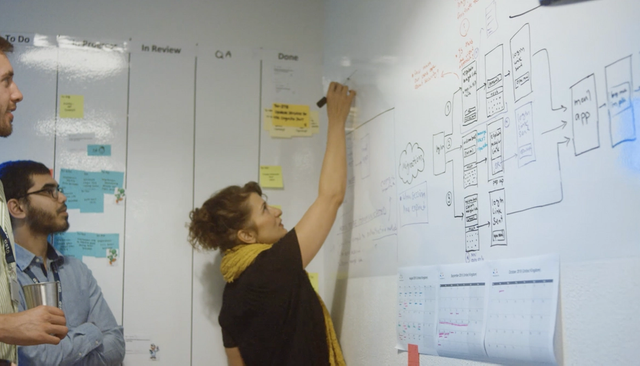 Woman writes on whiteboard as colleagues watch