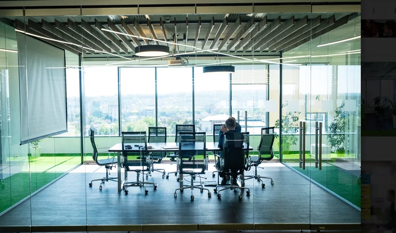 A colleague works in a large glass walled board room.