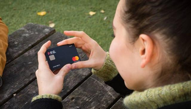 A woman looks at her P.F.C debit card