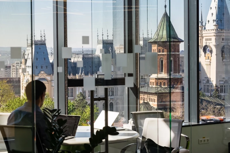 A colleague sits in a large office looking out on a picturesque skyline
