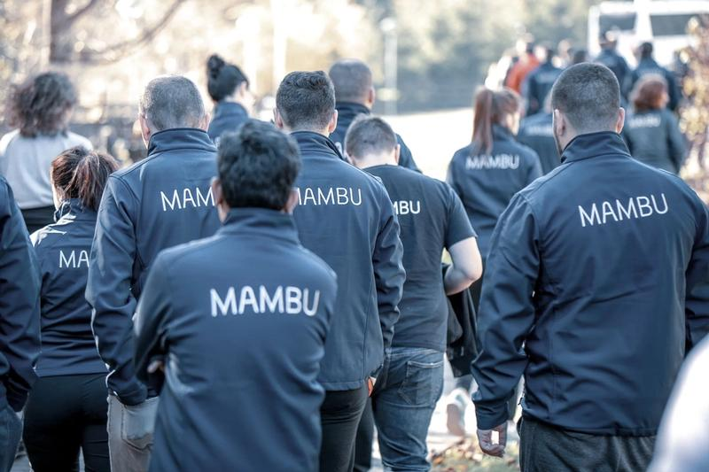 Team from behind wearing Mambu branded jackets.