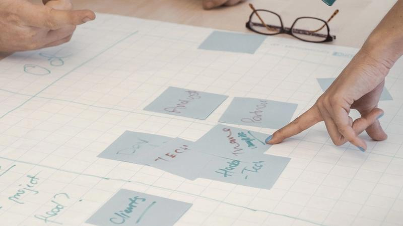 Someone points to a post-it note on a project plan.