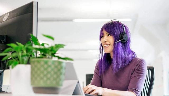 A woman sits a computer with a headset on.