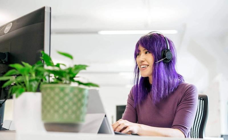 Woman with headset works in an open plan office