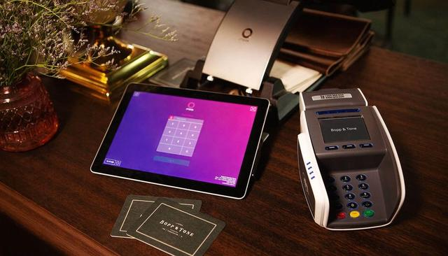 A tablet showing a pin input lies on a table next to a card reader