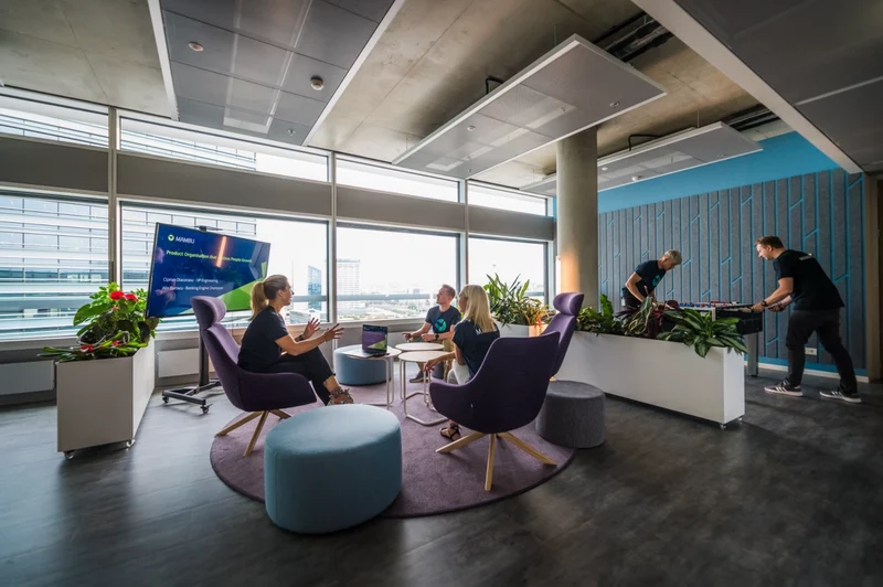 Some colleagues chat in an informal open plan space