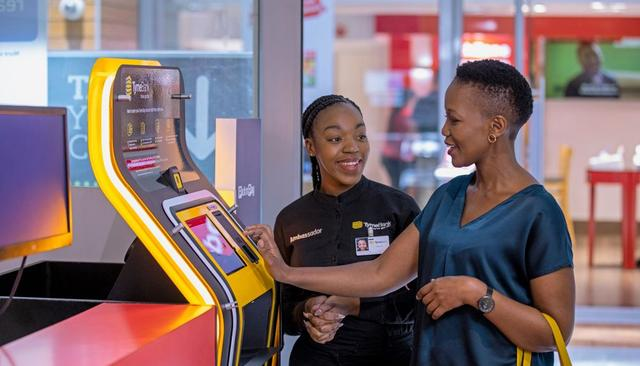 A customer stands at an in store cash machine while a friendly employee assists her.