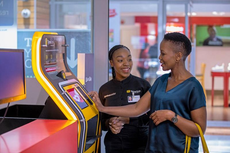 A member of staff helps a customer to use an instore atm