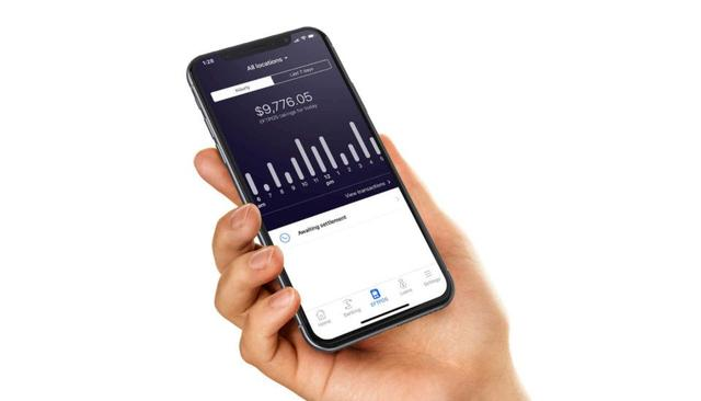 A hand holds a mobile phone showing a balance and a bar graph from the app