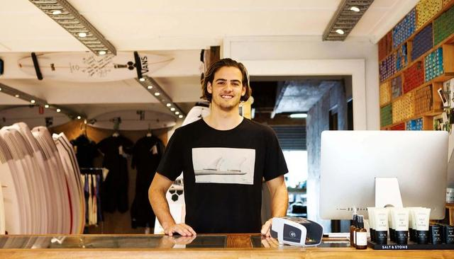 A man stands behind the counter in a surfing shop.