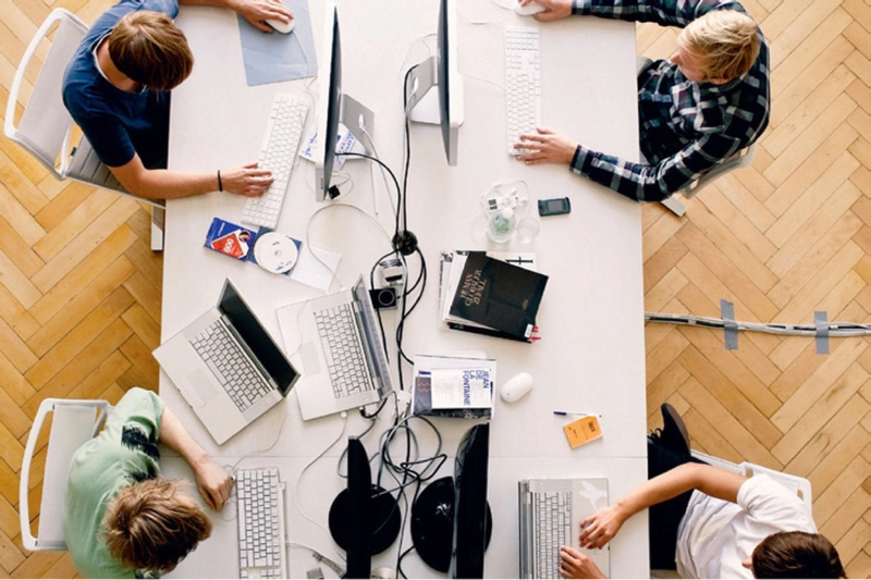 Aerial view of 4 people working at a shared desk.