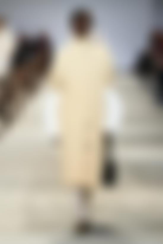 Model in cream coat and white under shirting