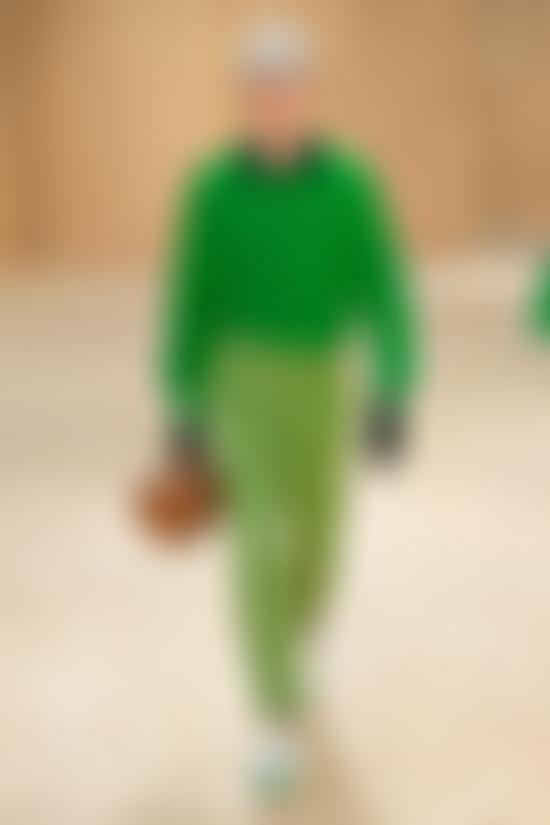 Model wears green shirt and trousers from Lacoste AW20