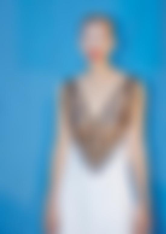 Model posing in white dress on a blue background