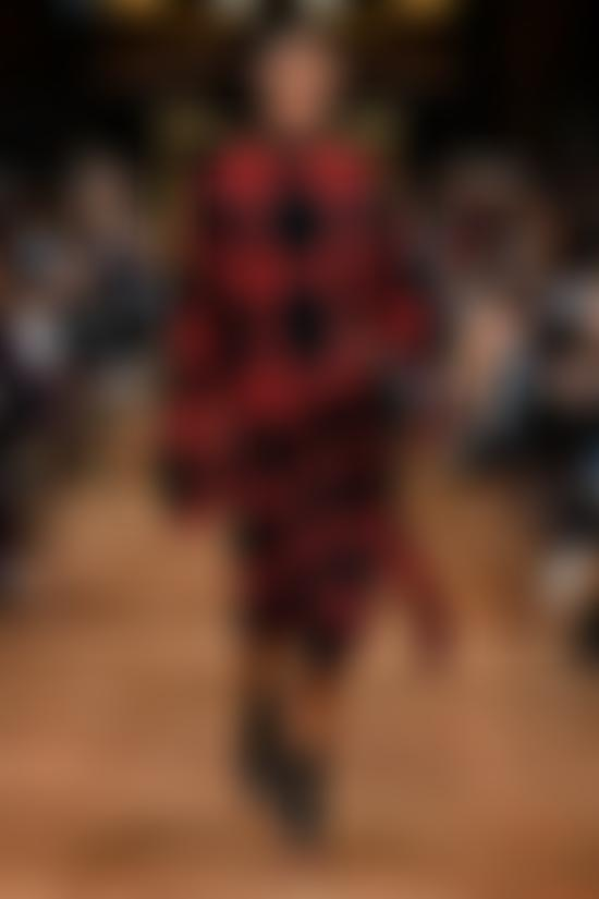 Model wears black and red check outfit on catwalk
