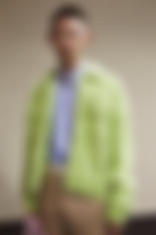 Model wears lime green cardigan by GCDS