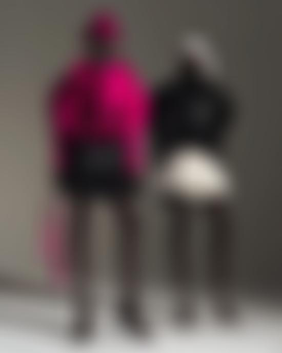 Models wearing pink jacket and top and black pleated skirt (left) and black leather top and white pleated skirt (right)