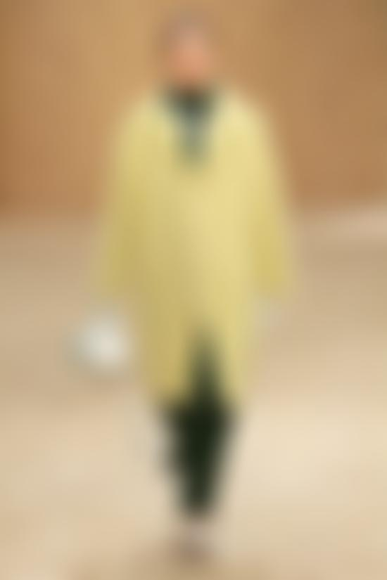 Model wears yellow coat and green trousers from Lacoste AW20