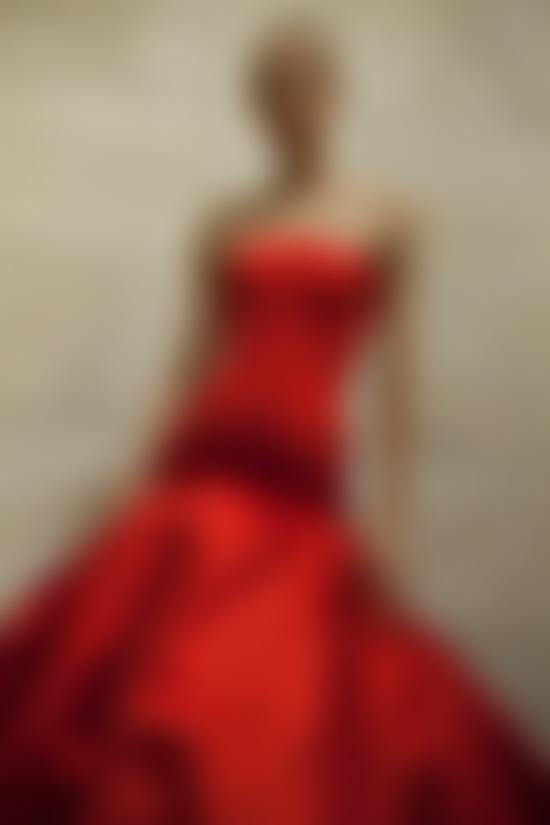 Model wears red strapless dress by Oscar de la Renta