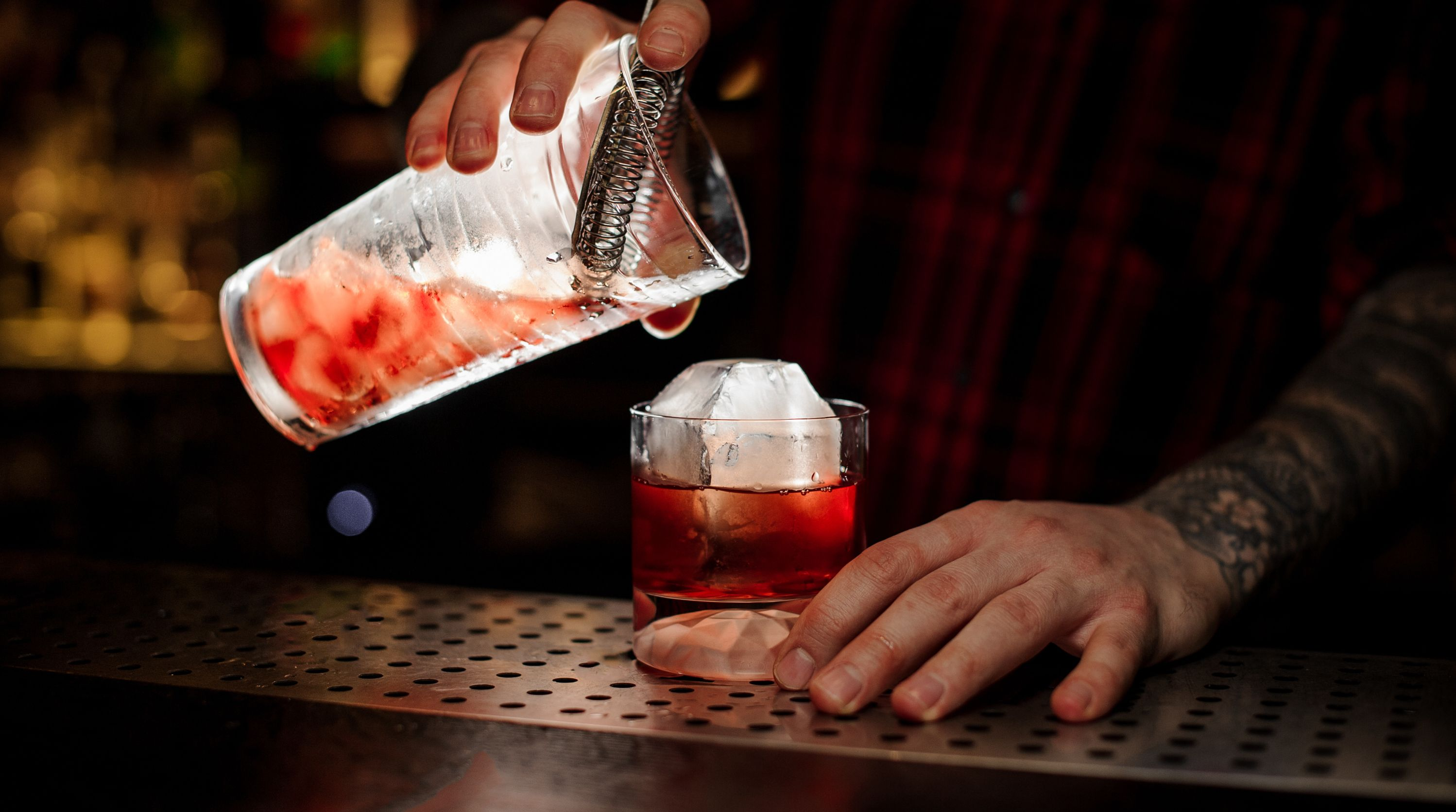 A bar tender pours a drink at the bar of a venue.