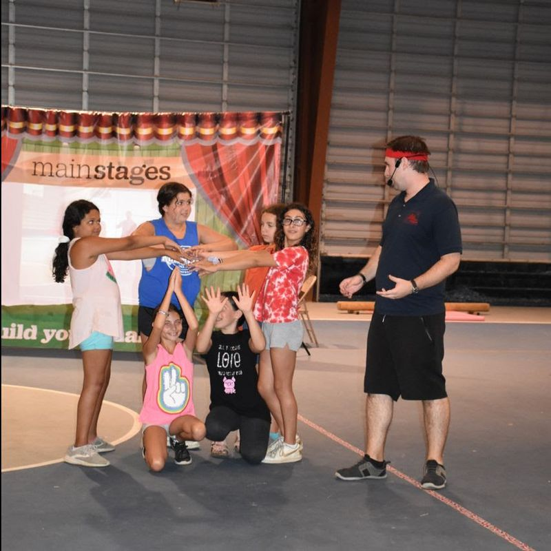 kids playing a theater game with a host at summer camp