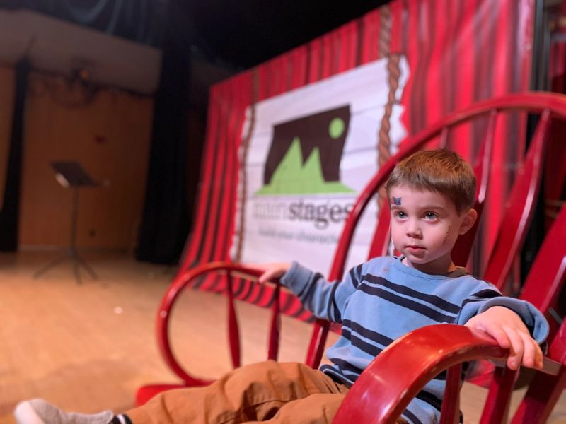 4 year old boy sitting on a red rocking chair in front of a mainstages backdrop