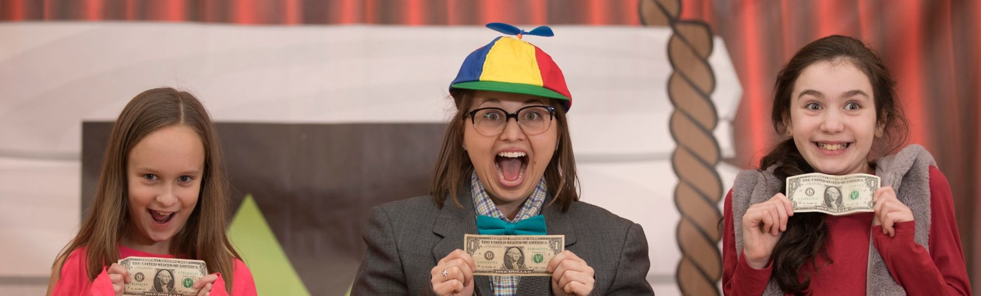 children's theater performer in a funny hat holding up dollar bills with two kids