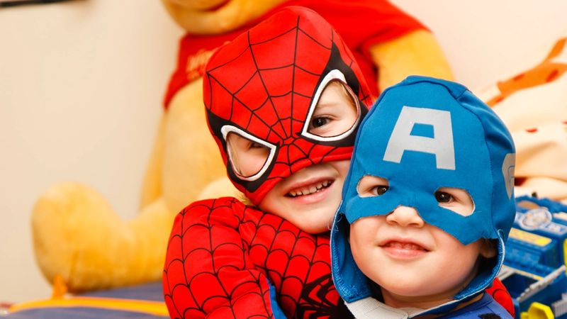 two young kids wearing super hero costumes hugging