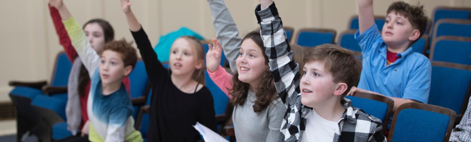 children with hands raised eager to answer a question