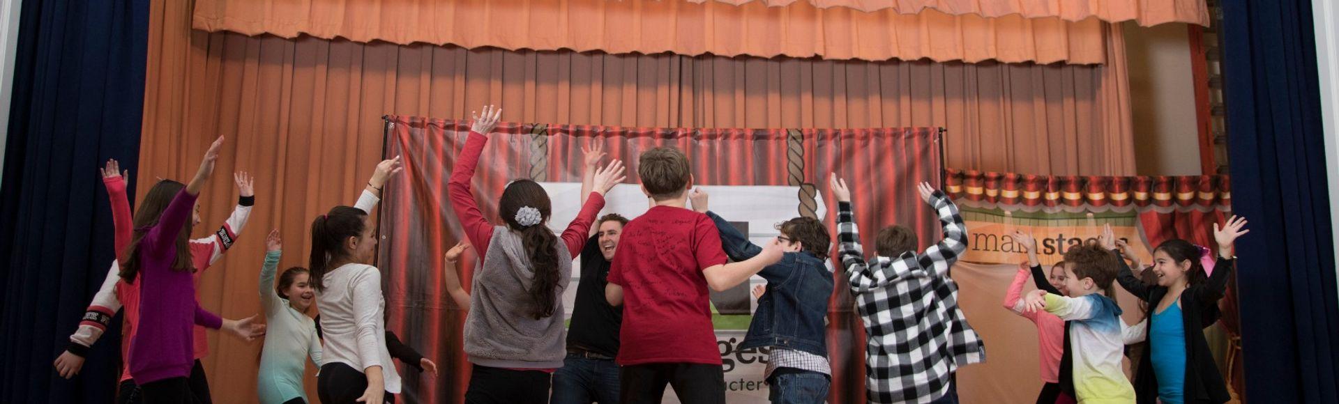 children jumping around on theater stage