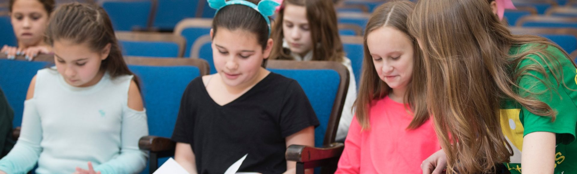 children sitting in audience seats reading theater scripts