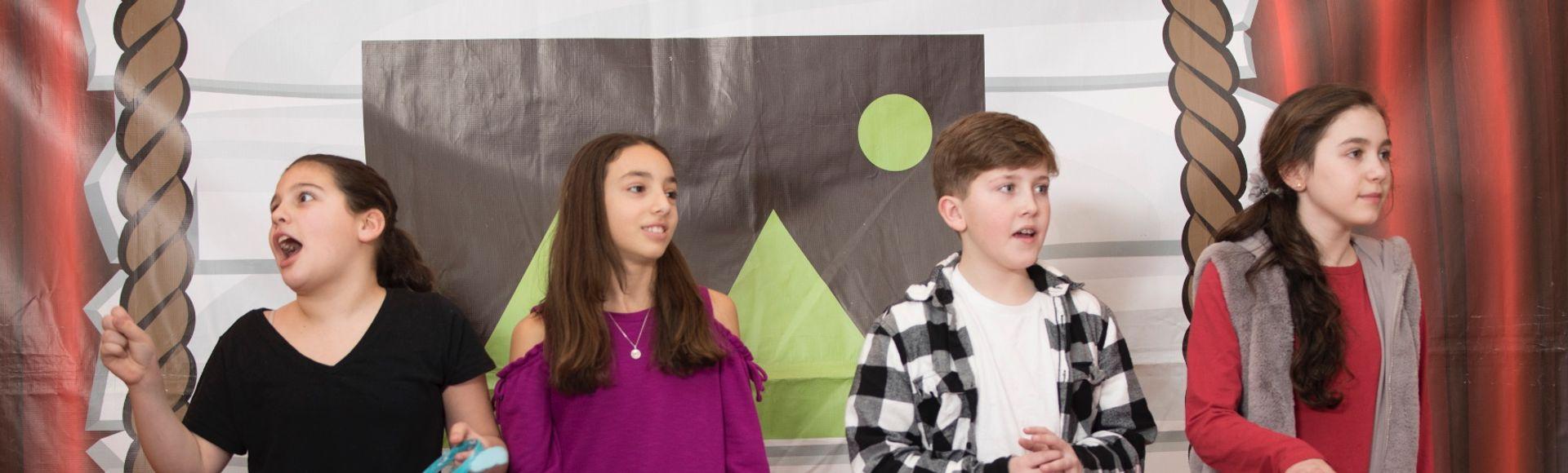 Kids standing behind buzzers