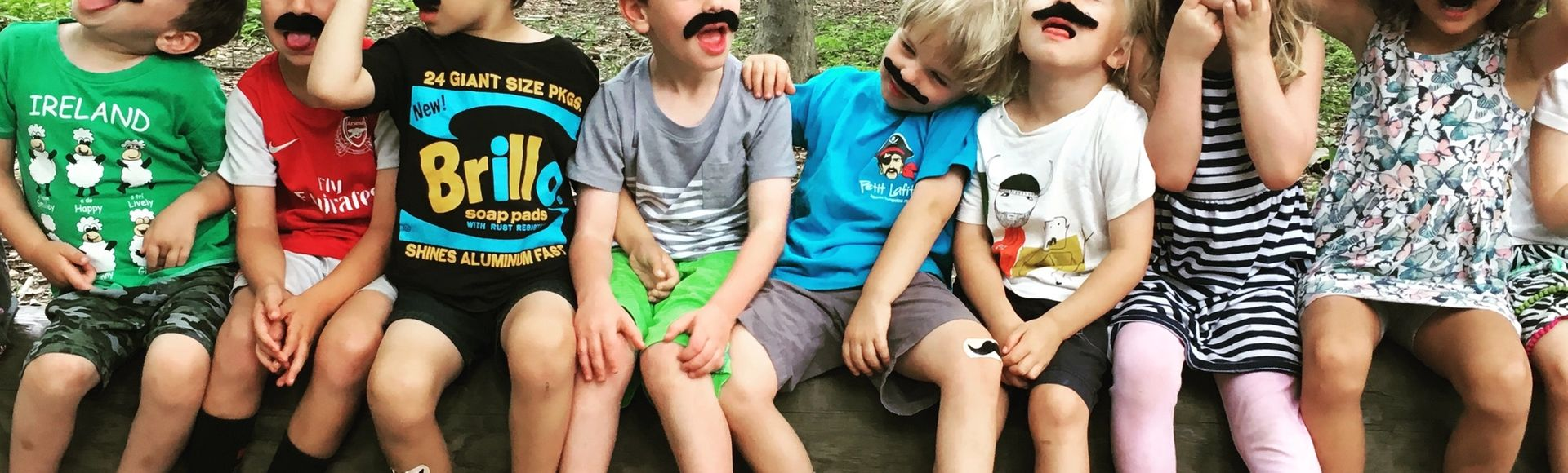kids at summer camp with fake mustaches on a log making silly faces