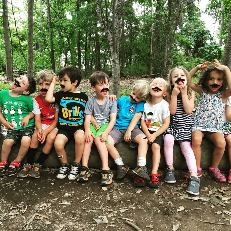 kids on a log at summer camp wearing fake mustaches