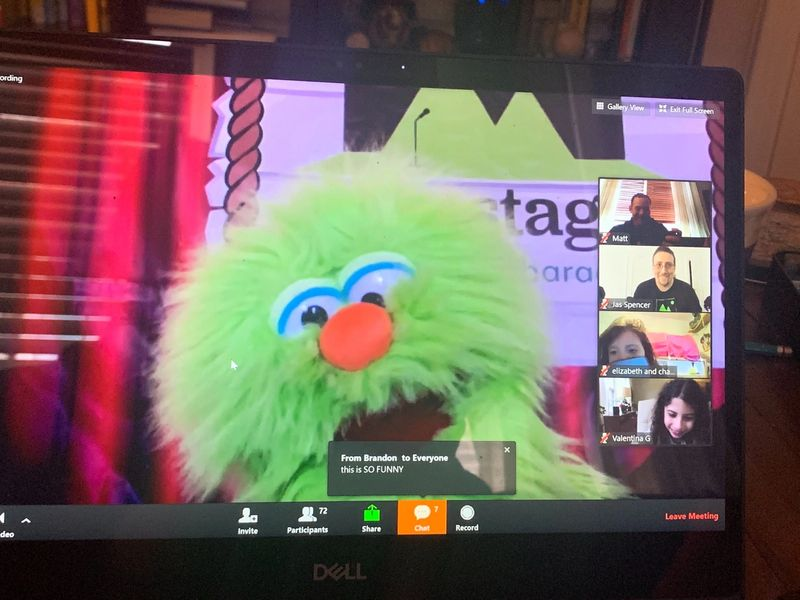 photo of a computer screen on zoom with a green puppet and kids on video chat