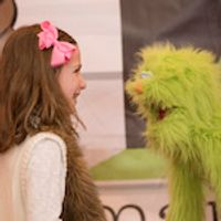 smiling little girl interacting with puppet operated by mainstages staff